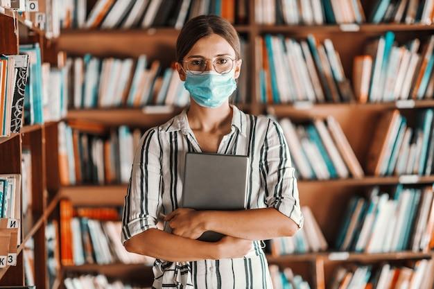 図書館に立ってタブレットを手に持ってフェイスマスクを持つ美しいインテリジェントな新入生の女の子。コロナウイルスの概念の間に遠隔研究。