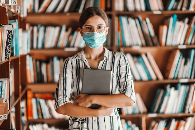 Beautiful intelligent freshman girl with face mask on standing in library and holding tablet in hands. remote studying during corona virus concept.