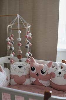 Красивый интерьер детской с детской кроваткой с подушками и розовым пледом