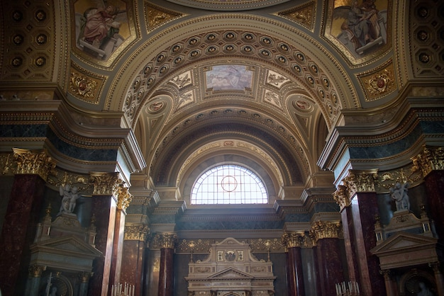 헝가리 부다페스트(budapest)의 벽과 대리석 조각상 및 조각에 화려한 그림이 있는 가톨릭 대성당의 아름다운 내부.
