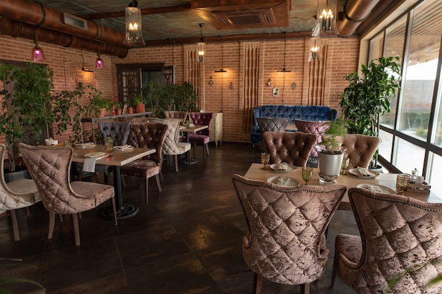 Beautiful interior of the restaurant in semiantique dark brown shades served tables