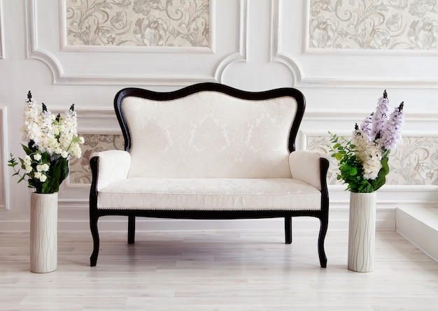 Beautiful interior - white sofa and flowers in vases