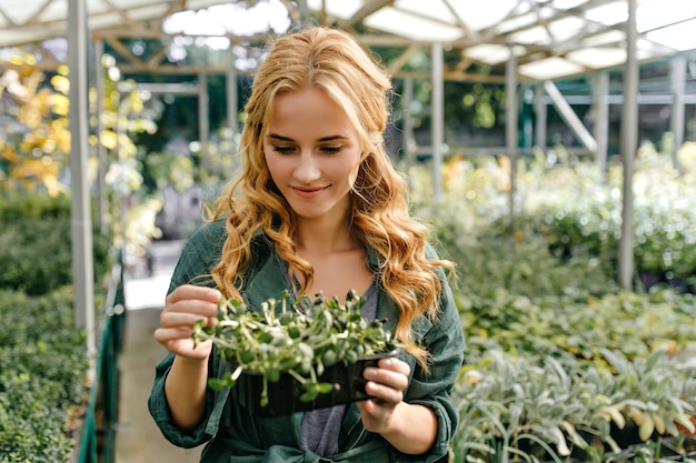 Beautiful irish red-haired lady nicely lowered her eyes, looking at plant. portrait of model in greenhouse.