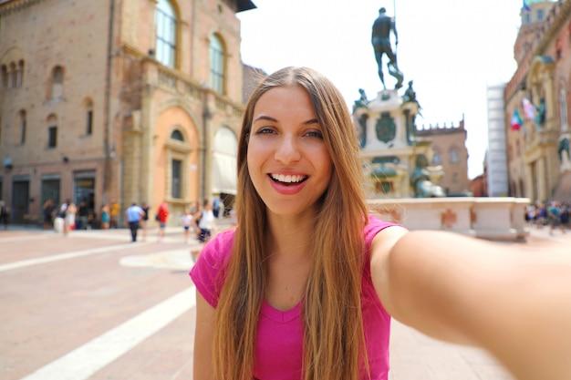 Прекрасная италия. привлекательная улыбающаяся молодая женщина принимает автопортрет на площади пьяцца дель неттуно в городе болонья, италия.