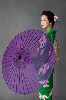 紫色の傘を持つ美しい日本のモデル