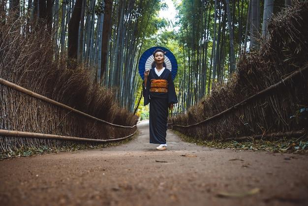 Красивая японская старшая женщина гуляя в бамбуковый лес