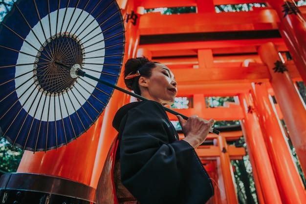 Красивая японская старшая женщина гуляя в святыню fushimi inari в киото