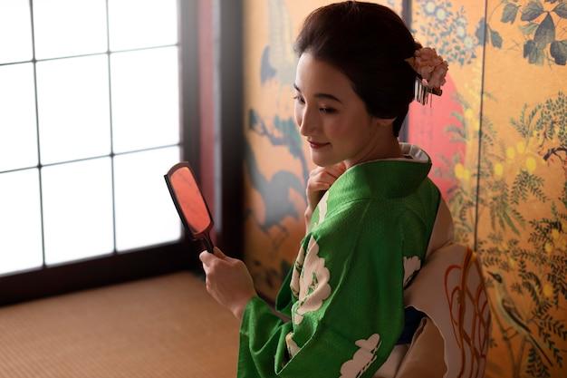 Красивая японская женщина смотрит в зеркало