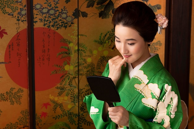 Bella donna giapponese che si guarda allo specchio