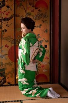 Красивая японская женщина надевает оби