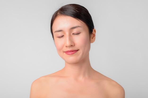 흰 벽에 건강과 미용 개념으로 벗은 아름다운 일본 여자