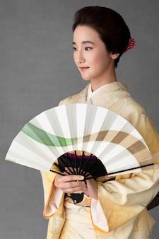 ミニマリストの扇子を持つ美しい日本人女性
