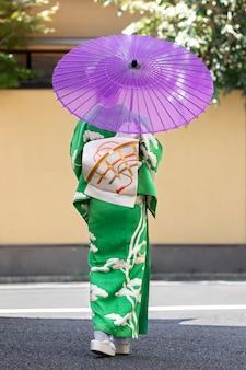 紫色の傘を持つ美しい日本人女性