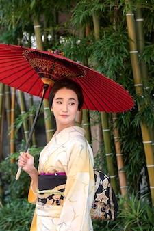 야외에서 빨간 우산을 쓴 아름다운 일본 여성