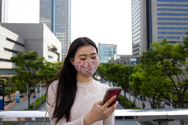 都会の環境で医療マスクを持つ美しい日本人女性