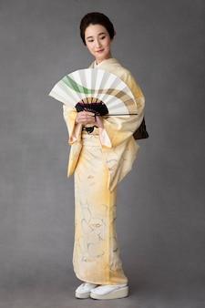 Beautiful japanese woman with a minimalist hand fan