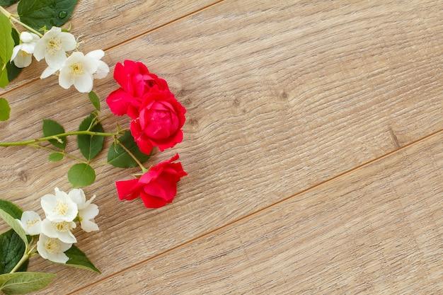 木製の背景に美しいジャスミンとバラの花。休日に贈り物をするという概念。コピースペースのある上面図。