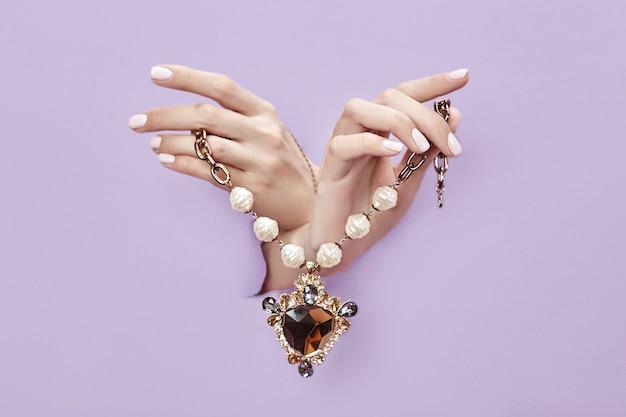 Красивые украшения на руках женщин, руки с браслетами и ожерельями торчат из разорванной фиолетово-лиловой бумаги.