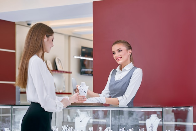 Beautiful jewelry store worker is showing a necklace to a female client of the shop