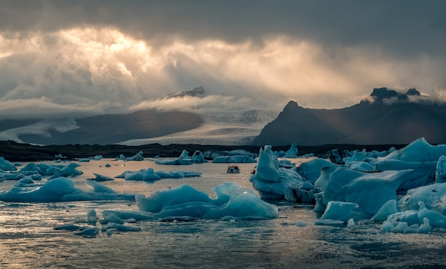 Beautiful jokulsarlon glacier lagoon in iceland, with sun beams from a dark cloudy sky