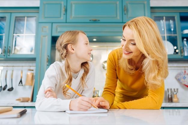 Красивая радостная светловолосая девушка улыбается и держит карандаш, глядя на свою мать, стоящую рядом с ней