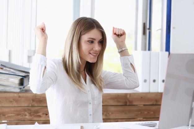 Красивая радостная женщина на рабочем месте с помощью компьютера