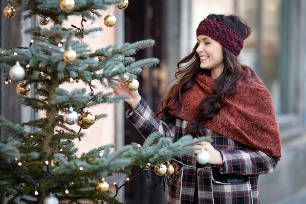 Beautiful joyful woman portrait in a city. smiling  girl wearing warm clothes and hat  in winter. christmas time with natural decorative fir tree