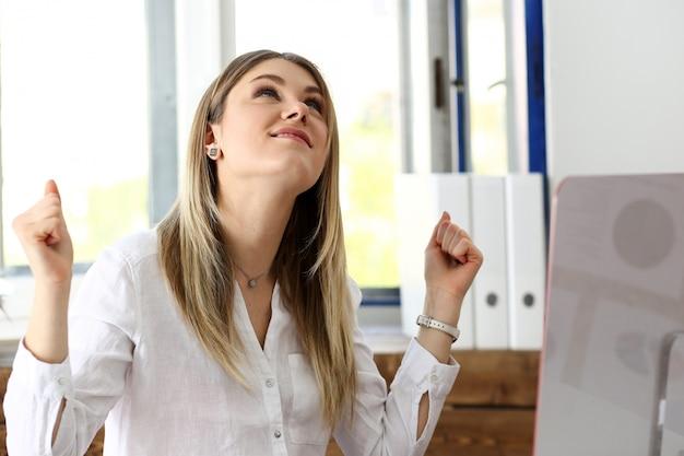 Beautiful joyful woman at workplace using computer pc