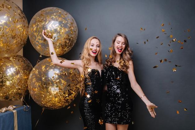 金色のティンセルを楽しんでいる黒い高級ドレスを着た美しい楽しい若い女性。素晴らしいパーティー、新年、大きな風船、お誕生日おめでとう、笑顔、陽気な気分を祝います。