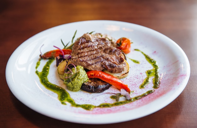 A beautiful juicy steak with salad on round plate is on the wooden table.