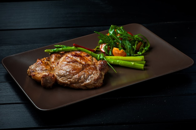 A beautiful juicy steak with salad on a straight brown plate is on the table.