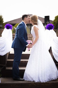 Beautiful just married couple standing face to face and kissing