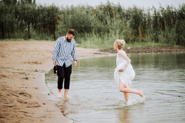 結婚したばかりの美しい人は、海岸線で楽しんで喜んでいます。