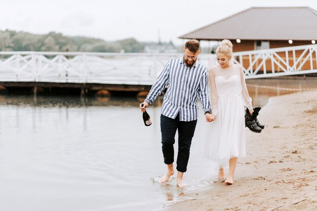 結婚したばかりの美しい美しい海岸線を裸足で歩き、手をつないでください。