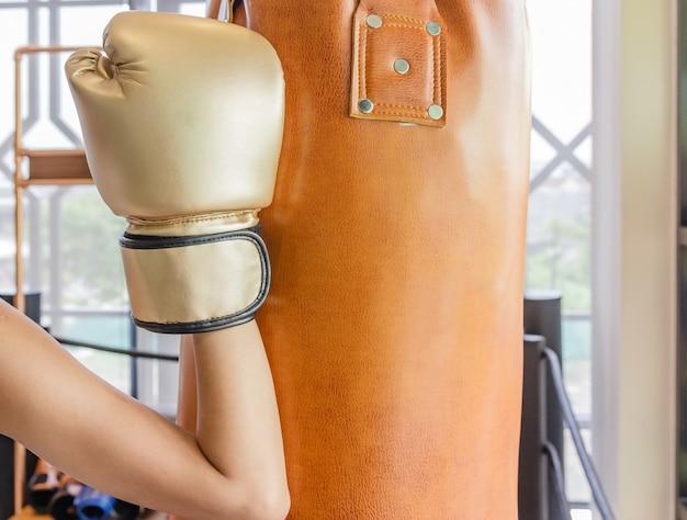 Beautiful kickboxing woman training punching bag in fitness studio