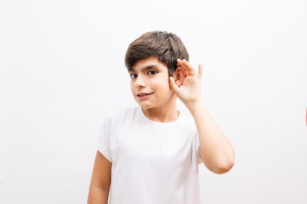 소문 또는 험담을 듣고 귀에 손으로 웃 고 격리 된 흰색 배경 위에 캐주얼 티셔츠 서 입고 아름 다운 아이 소년. 난청 개념.