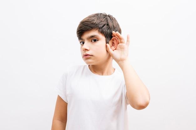 소문이나 험담을 듣고 귀에 손으로 고립 된 흰색 배경 위에 서있는 캐주얼 티셔츠를 입고 아름 다운 아이 소년. 난청 개념.