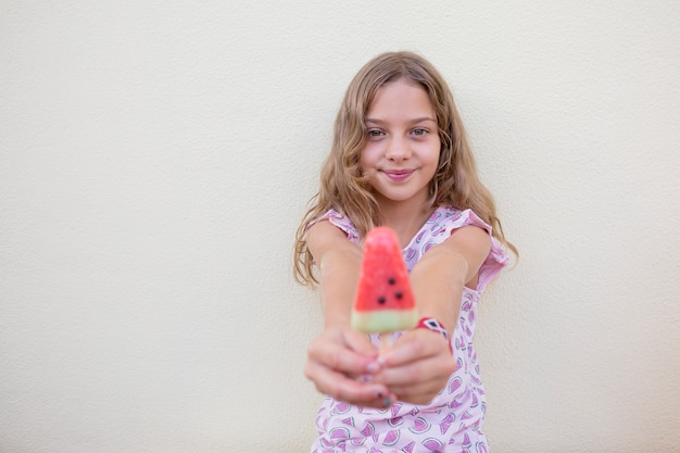 Beautiful kid girl eating watermelon over white wall. family love and lifestyle outdoors