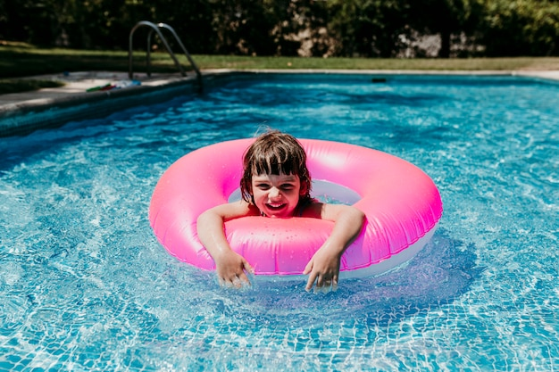 Beautiful kid girl floating on pink donuts in a pool. smiling. fun and summer lifestyle