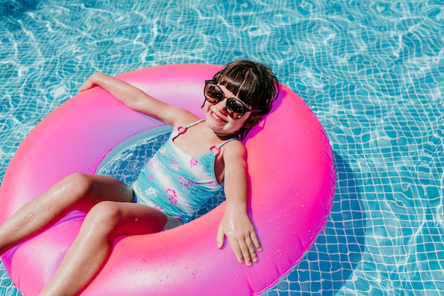 Beautiful kid girl floating on pink donuts in a pool. wearing sunglasses and smiling.
