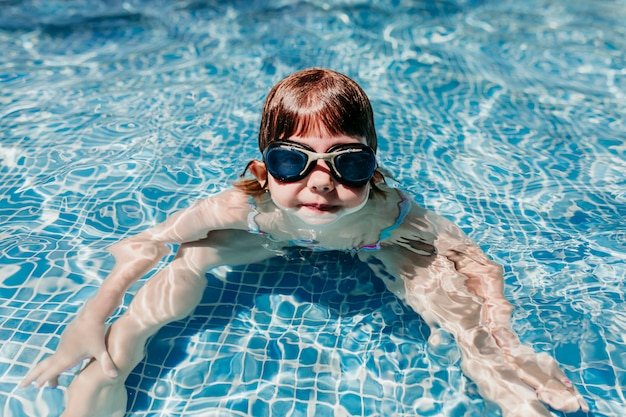 Beautiful kid girl at the pool diving with water goggles. fun outdoors. summertime and lifestyle concept
