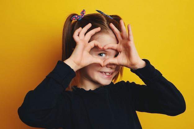 Красивая девочка улыбается и держит руки, руки, фигуру в форме сердца возле глаз