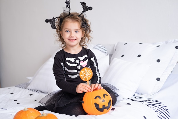 Beautiful kid girl in witch costume eating cookies in decorated for halloween bedroom