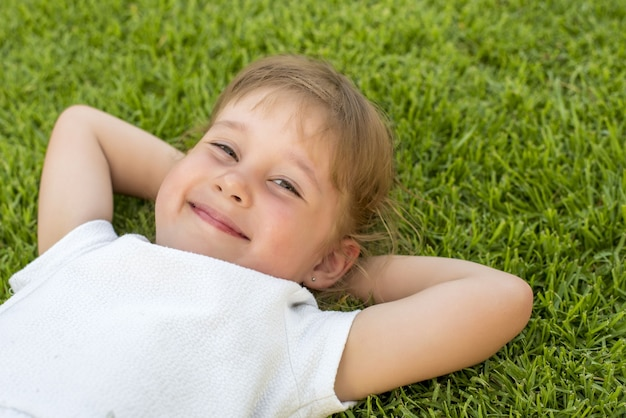 Beautiful kid laying on the grass in the park