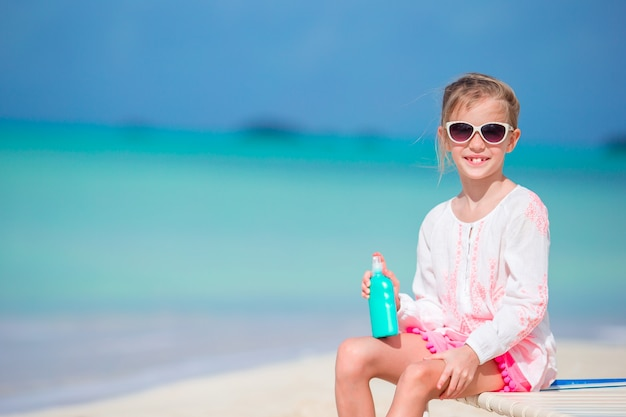 Beautiful kid with bottle of sun cream on tropical beach