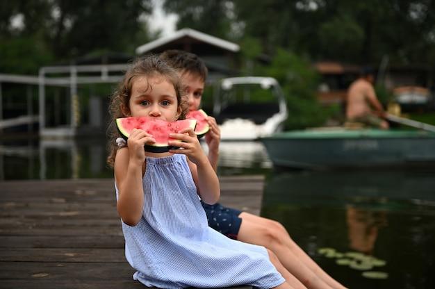 美しい子供たち、桟橋で男の子と女の子、休憩しておいしいジューシーなスイカを味わう。夏のアウトドアレクリエーション。夏休みに湖の背景に甘い健康的なスナックを取っている子供たち
