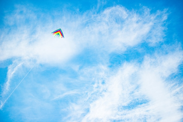 Beautiful kite in bright colors of the rainbow flies against a sunny blue sky.