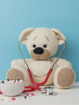 A beautiful knitted bear with a stethoscope and a large number of medications.