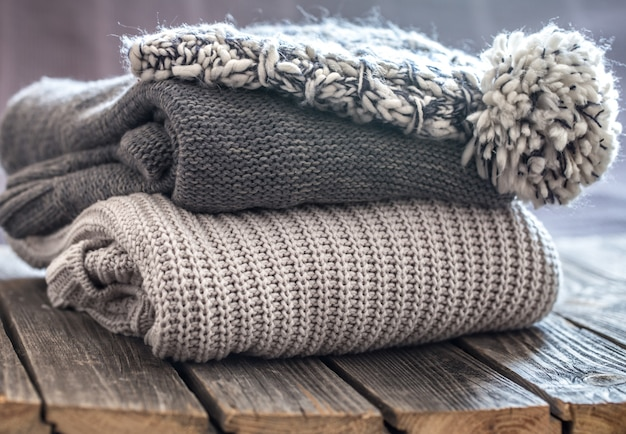 Beautiful knitted clothes, neatly folded, close-up, handmade sweaters.