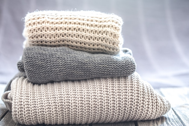 Красивая вязаная одежда, аккуратно сложенная, крупный план, свитера ручной работы.